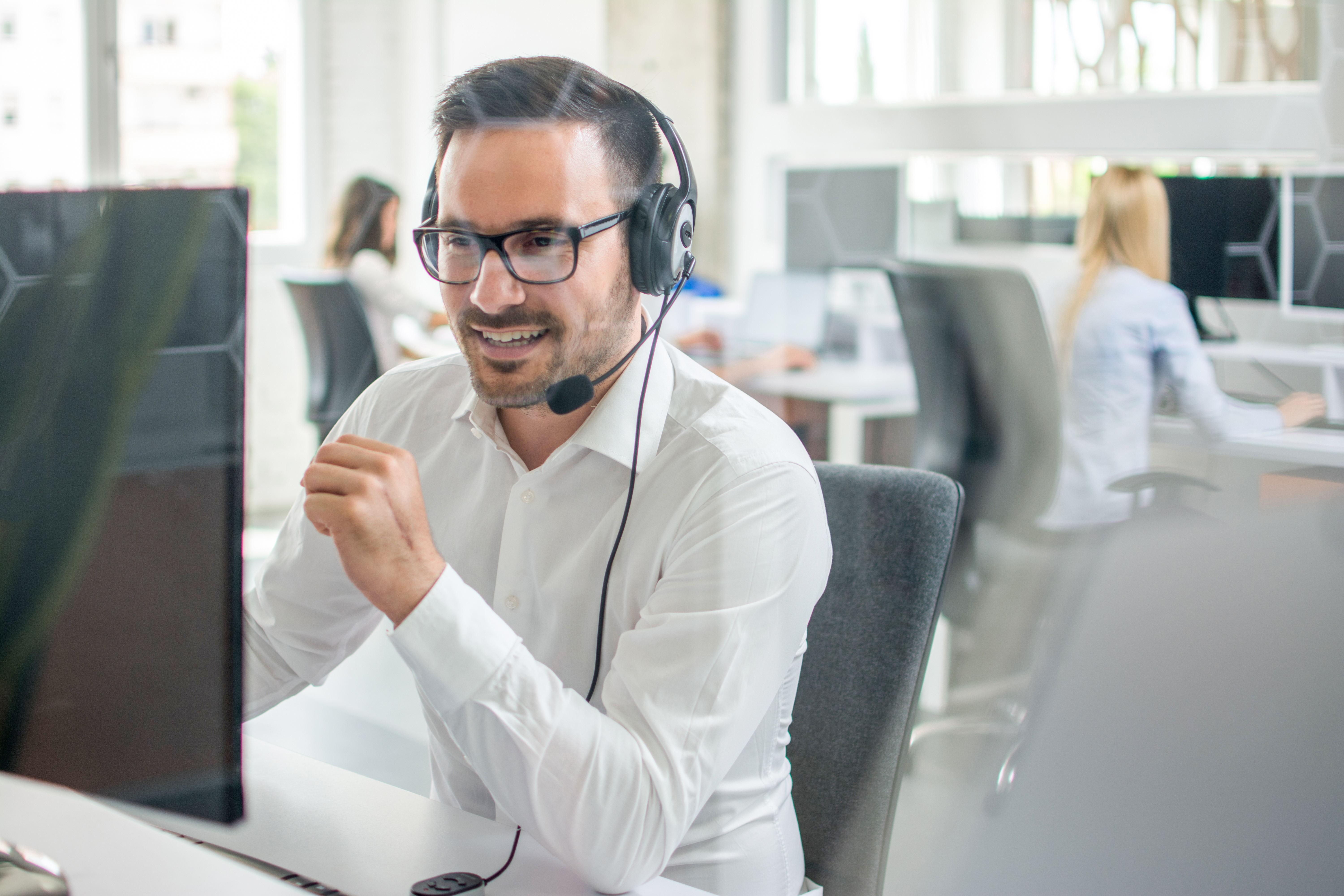 Customer service agent smiling on phone in office